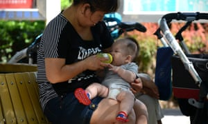 A woman feeds a baby with a bottle in a residential area in Beijing.