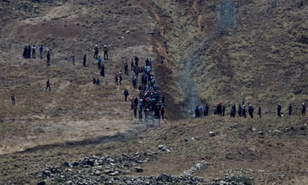 People in Syria walk towards the border fence with Israel