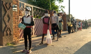 A queue forms outside Samantha Murozoki's home in Chitungwizaon May 5, 2020, where, with the help of volunteers, Samantha Murozoki serves over a 100 hot meals per day from her home to families whose household income has been cut off by closure of all informal markets during the lockdown