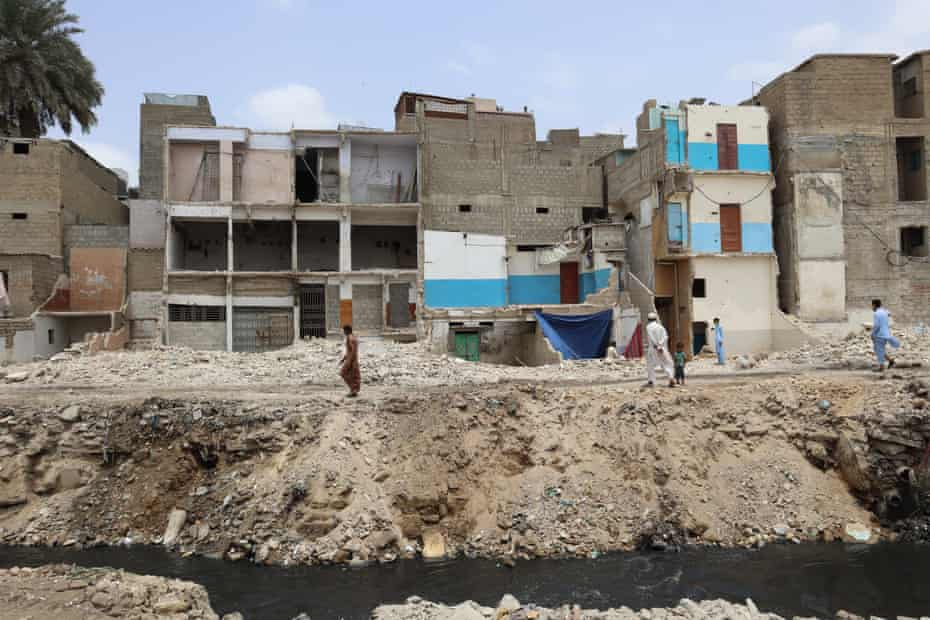 A man is walking on to  rubble where there used to be houses in Gujjar Nullah; houses in the background are seen damaged