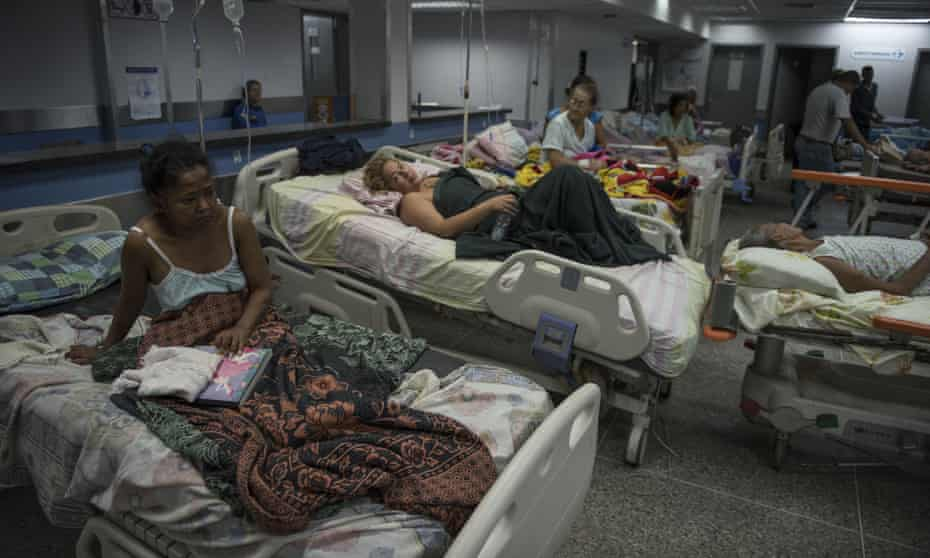 Patients lie on beds in the emergency room of a hospital in Barquisimeto, Venezuela.