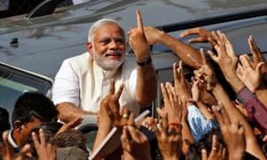 Prime minister Narendra Modi shows his ink-marked finger to his supporters after casting his vote in 2014
