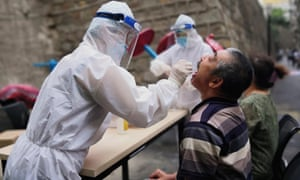 A medical worker takes a swab from  a citizen for testing in Urumqi
