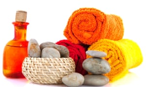 Rolled-up orange and yellow towels, a basket of stones and an orange bottle