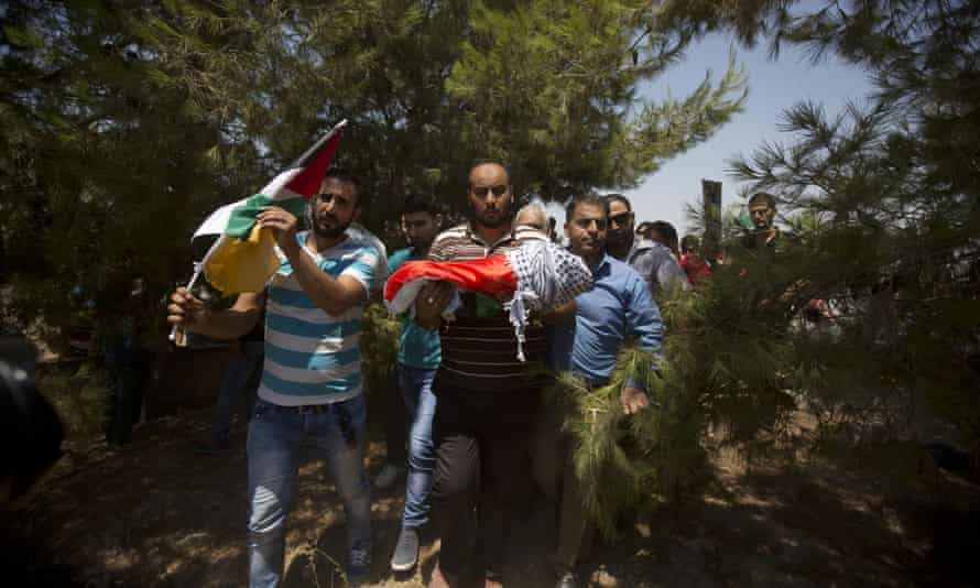 Palestinians carry the body of Ali Saad Dawabsha during his funeral in Duma village near Nablus. The sleeping toddler was burned to death in a fire at his home. (AP Photo/Majdi Mohammed)