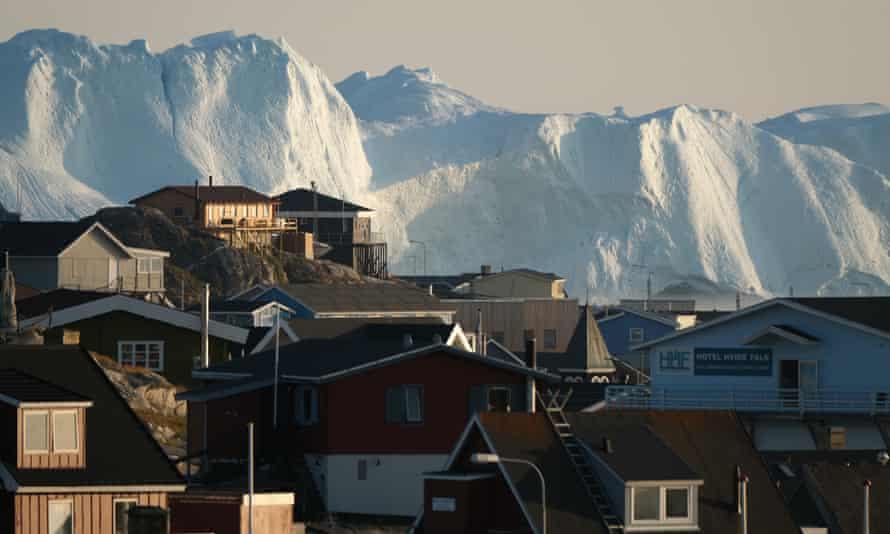 Icebergs loom behind buildings in Ilulissat, Greenland