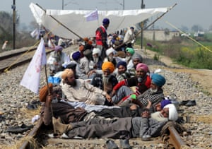 Farmers block railway tracks during a protest in Devi Dass Pura, a village near Amritsar in the Indian state of Punjab