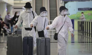 Passengers wear protective suits and face masks as they arrive at the Hong Kong airport. Only residents are now allowed to return.