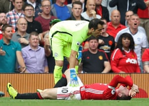 Manchester City's Claudio Bravo checks on a grimacing Wayne Rooney.