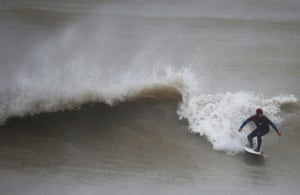 A surfer rides a wave as the wind wips spray off the wave off the coast at Newhaven