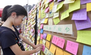 A woman posts a message on a wall near West Kowloon station.