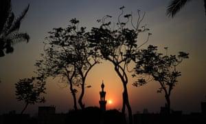 The sun sets over a minaret of a mosque at Al-Azhar Park, in Cairo, Egypt