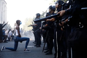 A protester takes a knee in front of police officers during a protest after the death of George Floyd.