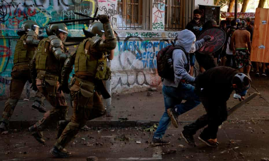 Riot police chases demonstrators during a protest against the government in Santiago on November 19, 2019.