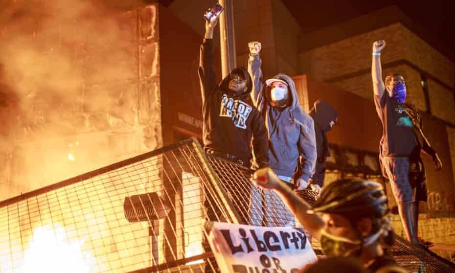 Protesters in front of the 3rd precinct station in Minneapolis. By the time the empty police station went up in flames, a handful of other buildings around it were on fire.