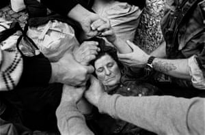 Aid workers and a British soldier help an elderly Bosnian woman who, having escaped from Banja Lucka during the Bosnian War, collapsed after getting off the bus which had brought her to safety in Travnik, Bosnia, April 1993