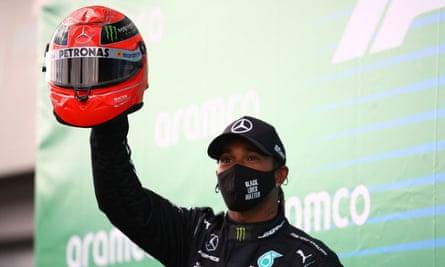 Lewis Hamilton dari Mercedes merayakan dengan helm merah milik Michael Schumacher setelah menang di Nürburgring.