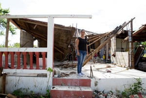 Norma Judith Colón stands in front of her damaged home after hurricane María.