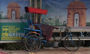 An Indian rickshaw cyclist sleeps next to an advertisement for a more environmentally friendly city, urging residents to switch to public transport, on a foggy morning in New Delhi