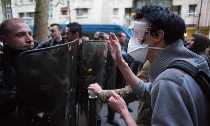 A policeman and protester come face to face outside the Jean-Jaurès high school in Paris.