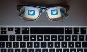 Twitter icon seen through glasses placed on laptop keyboard