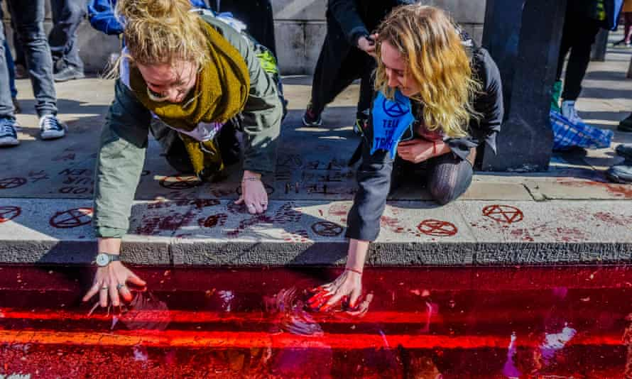 Extinction Rebellion activists pour 200 litres of (artificial) blood outside Downing Street.