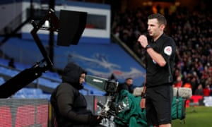 Michael Oliver checks the VAR pitchside monitor before showing a red card to Crystal Palace's Luka Milivojevic in the FA Cup.