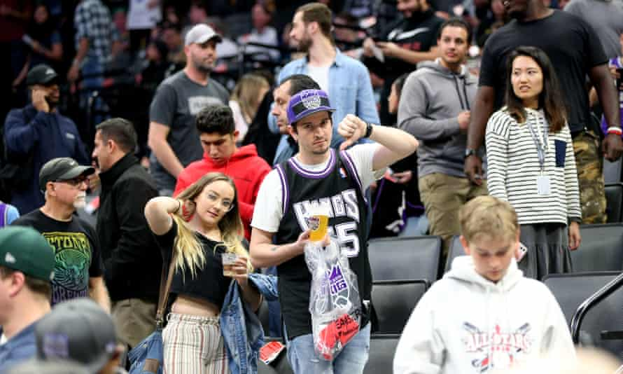 NBA fans make their way out of the arena after it was announced that the New Orleans Pelicans-Sacramento Kings game had been postponed, and the league suspended