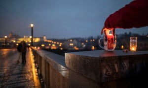 A man lights a candle in a beer glass on the bridge in the Old Town district amid the COVID-19 pandemic on January 03, 2021 in Prague, Czech Republic.