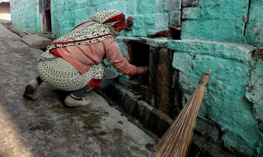 A manual scavenger cleaning a dry toilet in TK1 village near Agra, Uttar Pradesh