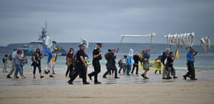 Police officers walk with activists on the Extinction Rebellion climate crisis protest march on the beach in St Ives, with a naval vessel in the background.