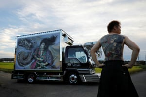 Truck driver Hideyuki Haga poses in front of his vehicle, which is decorated with the same design as the tattoo on his back, in Hiki, Saitama prefecture. 'When this painting was done I think I was about as excited as when my tattoo was done. The tattoo is now part of myself. I definitely feel proud of it.'