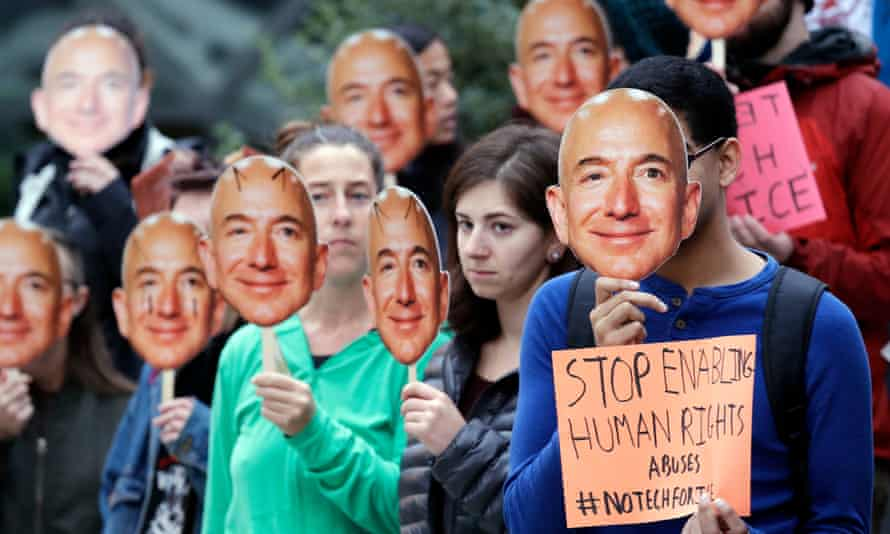 Demonstrators hold images of Amazon CEO Jeff Bezos near their faces during a Halloween-themed protest at Amazon headquarters over the company's facial recognition system last year.