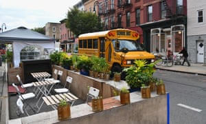 A school bus passes by empty tables of a restaurant in the Brooklyn Borough of New York City last week.