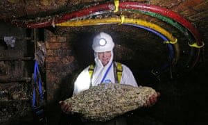 A 'flusher' holds a fatberg in a London sewer.