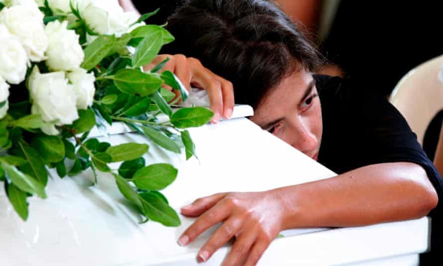 Girl hugs coffin