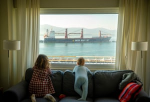 Santander, Spain Two children look at the merchant ships docking at the port from the window of their house during the emergency lockdown