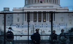 A Capitol police officer stands with members of the National Guard behind a crowd control fence surrounding Capitol Hill on Thursday in Washington DC.