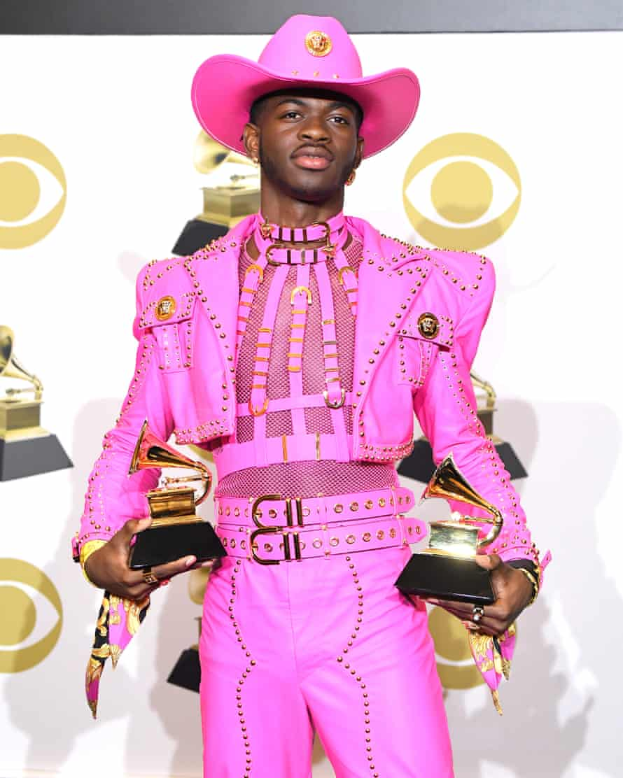 Lil Nas X wearing a leather, Barbie-pink Versace suit, with a harness, see-through mesh T-shirt and cowboy hat, holding two awards at the Grammys in January 2020