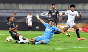 Yassine Bounou of Sevilla FC makes a save from Anthony Martial.