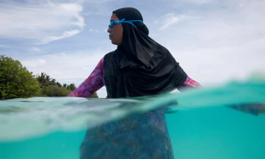 Take the plunge: a woman from the Maldives joins in with the the Soneva Fushi Learn To Swim programme, wearing robes and a headscarf.