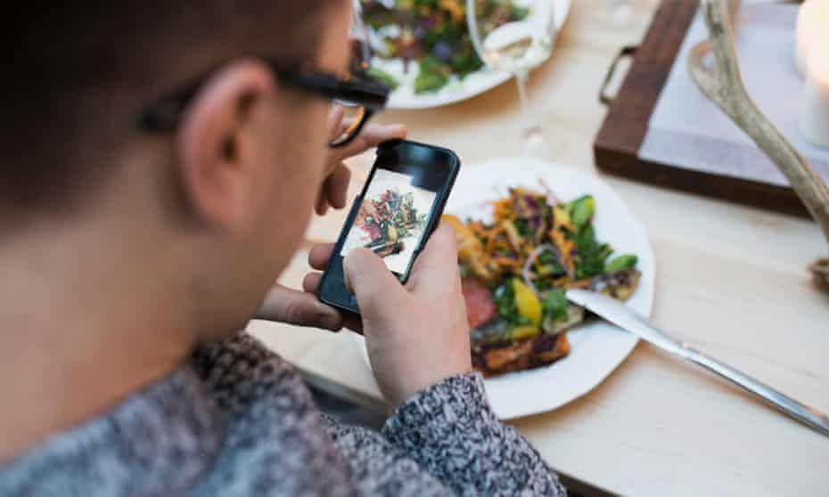 A man photographing a plate of food in a restaurant
