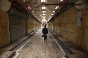 A man walks by closed shops in Nablus
