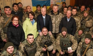 US ambassador to Ukraine Marie Yovanovitch, US senators Amy Klobuchar, John McCain, Ukraine's president Petro Poroshenko and US senator Lindsey Graham (left to right at center) pose for a photograph with Ukrainian servicemen.