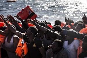 People thought to be from Nigeria, the Gambia and Senegal wait rescue from a boat in the Mediterranean, north of Libya