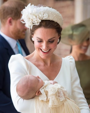 The Duchess of Cambridge wearing a headband as she carries Prince Louis for his christening service in July.