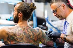 A tattoo artist works on a man's tattoo International Tattoo Festival, London