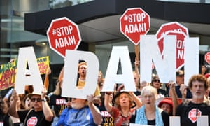 Anti Adani protesters hold signs outside the company's offices in Brisbane, Australia, 13 September 2018.