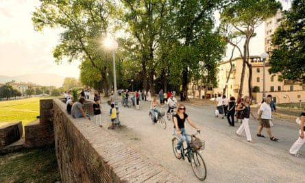 A woman cycles along the historic walls, as the sun is setting behind her, in the Italian city of Lucca.