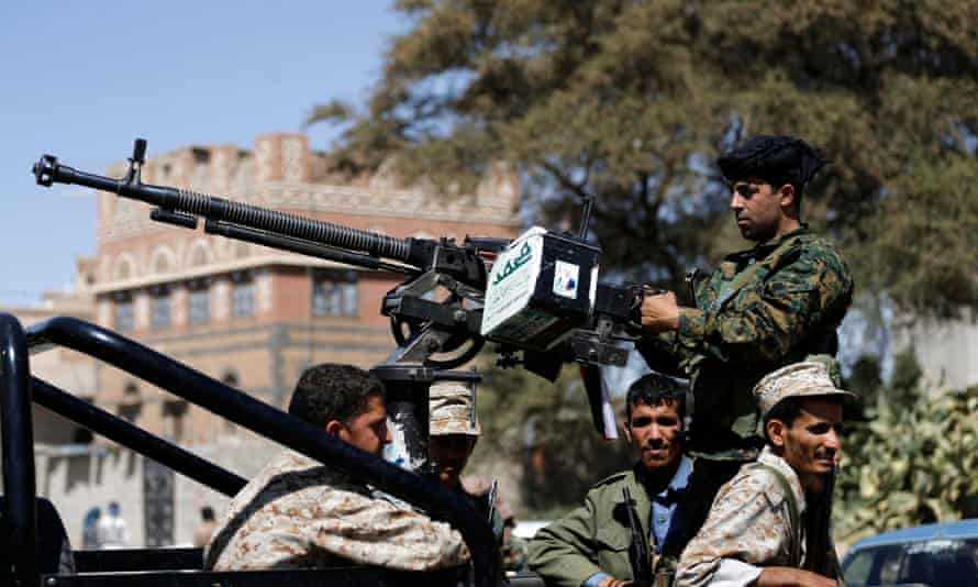 Houthi fighters ride a patrol truck in Sana'a.